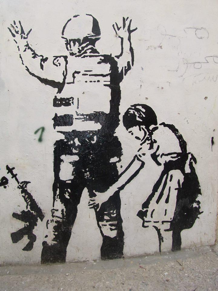 Murales di bambina che  perquisisce soldato